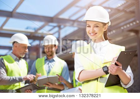Pretty engineer. A cheerful and content female engineer standing with papers with a group of engineers in a background being in construction site