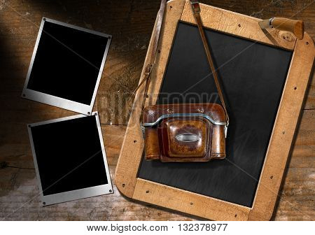 Vintage camera with leather case two empty instant photo frames and a blank blackboard with wooden frame on a wooden wall