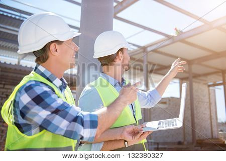 Sideward glance.  Cheerful and glad engineers looking at a worker and poking at him while holding a laptop with plans about construction works