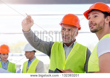 Future building plan. Cheerful and content pair of engineers standing together and thinking about future construction with another pair of engineers in a background