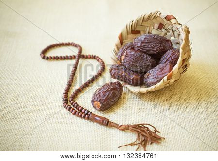 Fine quality Mejdool dates in a earthen basket with wooden islamic rosary.