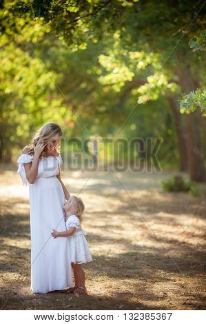 Beautiful pregnant woman with young daughter in green garden