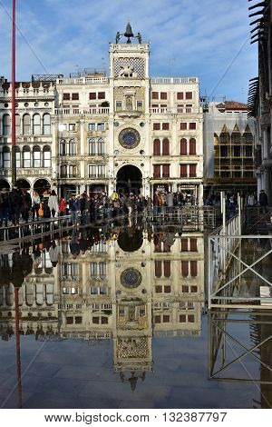 VENICE, ITALY - NOVEMBER 28: High tide flooding Saint Mark Square in Venice and tourists walking on footbridge before the famous Clock Tower