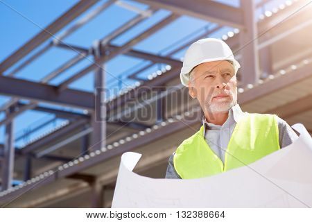 Skilled specialist.  Thoughtful and busy architect in helmet standing near new undone building and thinking about project