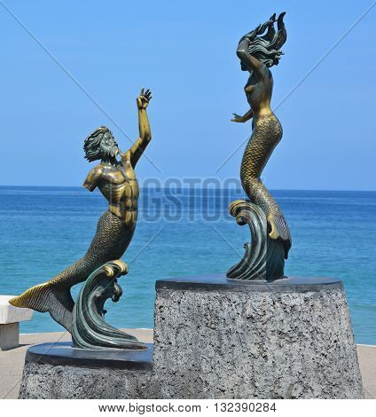 PUERTO VALLARTA MEXICO MAY 07 2016: Statue on the corner of Abasolo and the Malecon. This sculpture by Carlos Espino, Triton and Mermaid, concentrates on the human form and classical mythology,