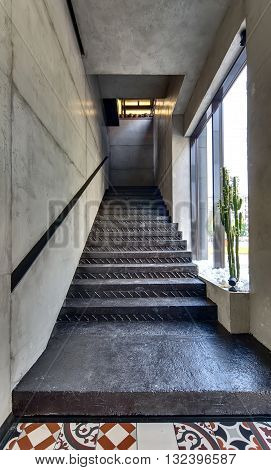 Black stair with black handrail in a restaurant. On the sides there are concrete walls. On the right there is a window and a big cactus. In front of the stair there are figured tiles on the floor. At the end there is a niche with the pots. Vertical.