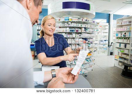 Pharmacist Explaining Details Of Product To Customer