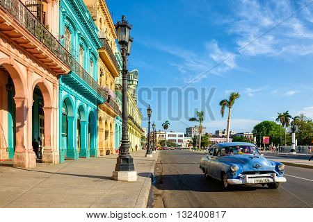 HAVANA,CUBA - MAY 26,2016 : Street scene with colorful buildings and old american car in downtown Havana