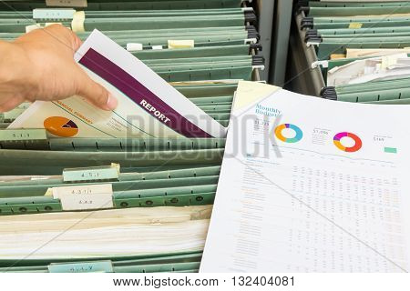 Hand holding report chart file in filing cabinet poster