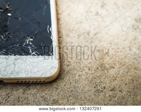 Close up of broken mobile phone or tablet droped on cement floor with copy space High contrast