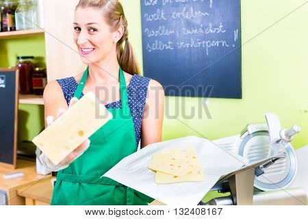 Saleswoman at organic supermarket counter offering cheese
