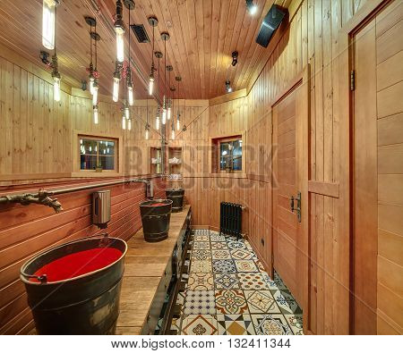 Washroom with wooden walls in a mexican restaurant. On the left there are metal-red washbasins in the form of buckets, soap dispensers, metal faucets in the form of a fairy animal, a big mirror. Opposite wall reflected in the mirror.