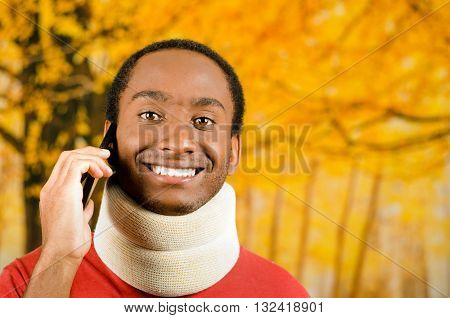Injured young positive black hispanic male wearing neck brace and smiling to camera, yellow abstract background.