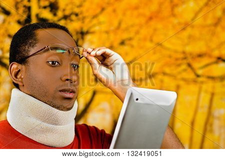 Injured young positive black hispanic male wearing neck brace, holding tablet and reading from screen lifting glasses up forehead, yellow abstract background.