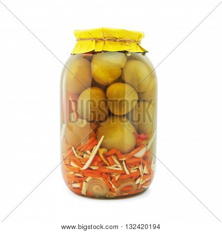 Homemade pickled green tomatoes with carrots, garlic, onions and horseradish in glass jar with yellow paper wrapper. Homemade preserves, pickles. Jar of canned marinated tomatoes isolated on white