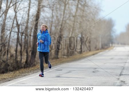 Runner woman running on road in beautiful nature. Jogging training for marathon