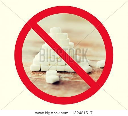 food, junk-food, diet and unhealthy eating concept - close up of white sugar pyramid on wooden table over red circle-backslash no sign