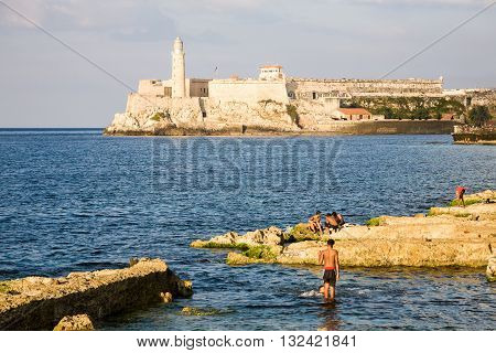 Havana Cuba - 2012 December 10 : Some cuban kids swimming in front of the Malecon with the El Morro castle in the background Havana