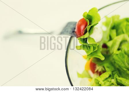 diet, vegetable food, healthy eating and objects concept - close up of vegetable salad with cherry tomato and lettuce in glas bowl