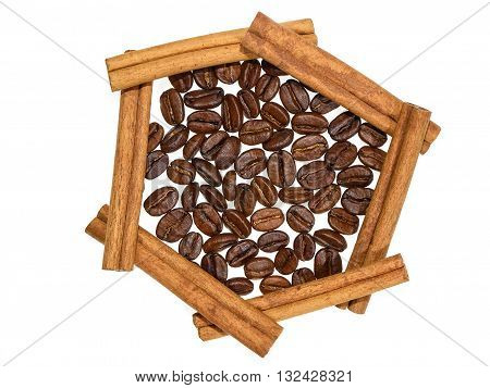 Roasted coffee beans in hexagon of cinnamon sticks on white background
