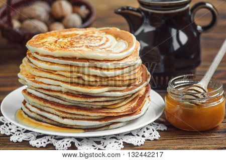 Stack of delicious, homemade pancakes with honey on white plate on wooden background. Healthy breakfast, close up.