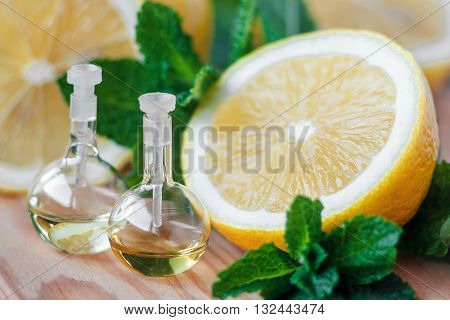Essential oil in glass bottle with fresh, juicy lemon fruit and green leaves of mint on wooden background. Beauty treatment. Spa concept. Selective focus.