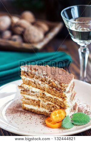Slice of homemade layered honey cake with mint, kumquat and walnuts, traditional food of Jewish New Near. Sweet food