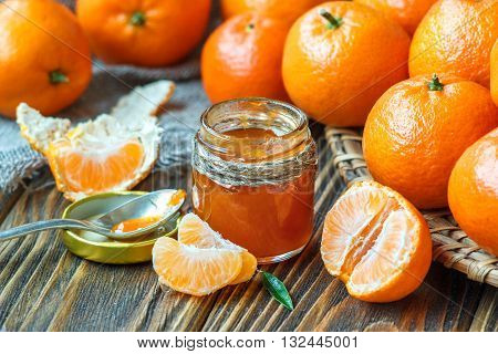 Homemade tangerine jam in glass jar with fruit around on a wooden table