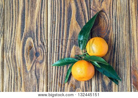 Tangerines with leaves on rustic wooden table with copy space. Top view.