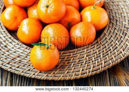 Fresh tangerines with leaves on wicker plate over old wooden table.