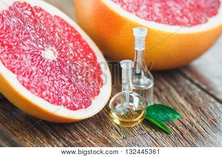 Essential oil in glass bottle with fresh, juicy grapefruit and green leaves-beauty treatment. Spa concept. Selective focus.