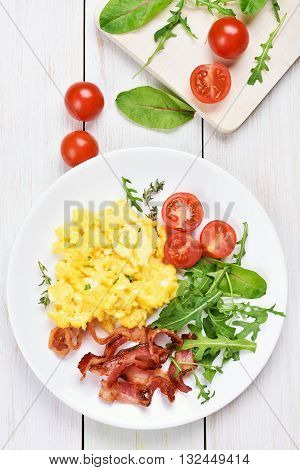 Breakfast with scrambled eggs bacon and vegetable salad on white wooden background top view