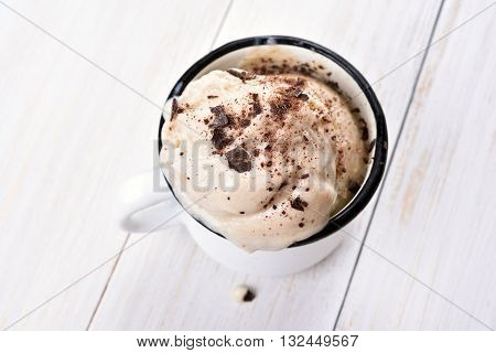 Summer dessert homemade banana chocolate ice cream in cup on white wooden background