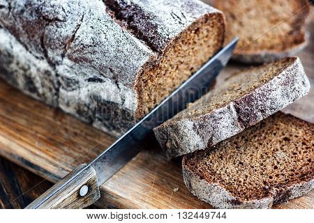 Sliced bread and knife. Loaf of bread with first half already cut into slices.
