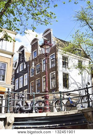 Old houses, bridge and bicycles in Amsterdam. Urban scene with blue sky and green tree.