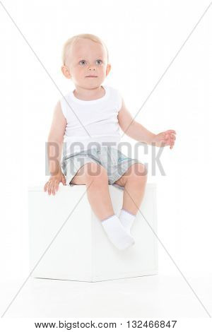 Serious yearling baby boy sits on cube on a white background.
