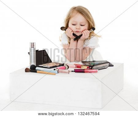 Pretty little girl playing with cosmetics on a white background. 3 year old.