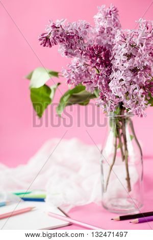 bouquet of spring flowers in glass bottle on a pink background. sheer fabric napkin and color pensils. Greeting card. Vertical.