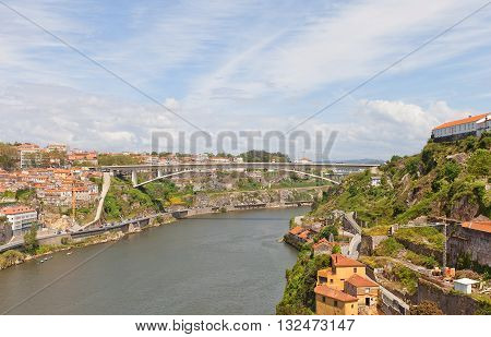 PORTO PORTUGAL - MAY 25 2016: Infante D. Henrique Bridge over Douro River in Porto city (UNESCO site) Portugal. Deck-stiffened arch bridge was erected in 2002