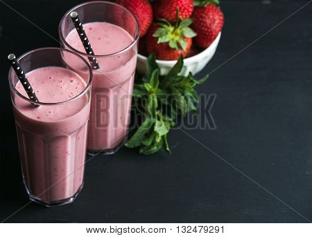 Strawberry and mint smoothie in tall glasses, bawl of fresh berries on dark rustic wood background. Selective focus, copy space