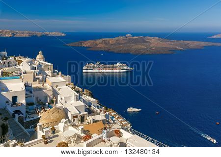 Fira, modern capital of the Greek Aegean island, Santorini, with orthodox church, cruise ships, caldera and volcano, Greece
