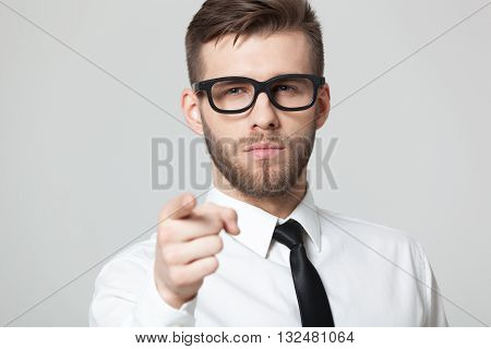 Young Handsome Businessman Pointing At You  Isolated On Gray Background.