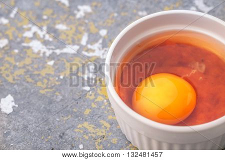 Raw eggs with tomatoes in the ramekins on the stone table