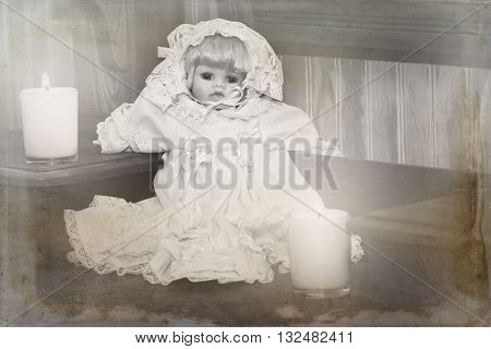 Distressed photo of a little creepy china doll and candles.