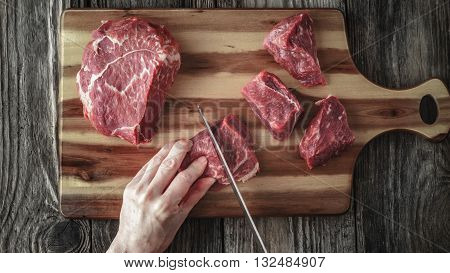 Cutting angus beef on the wooden table top view