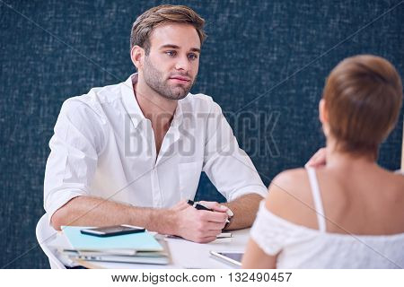 Man paying close attention to the woman he is having a meeting with as she explains the details of her business plan to him.
