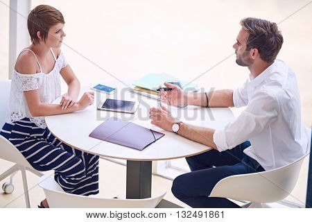 Young aspirational female entrepreneur getting professional business advise from a successful business and financial consultant while seated at a round table.