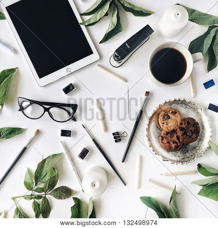 Workspace with tablet glasses cup of black coffee cookies on golden tray pencils paintbrushes and leaf. Flat lay composition for bloggers magazines social media and artists. Top view.