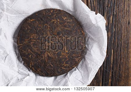 Chinese pu-erh tea on rice paper on a wooden table top view