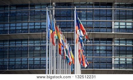 Front view of all members European Union flags waving in front of European Parliament building on a beautiful morning